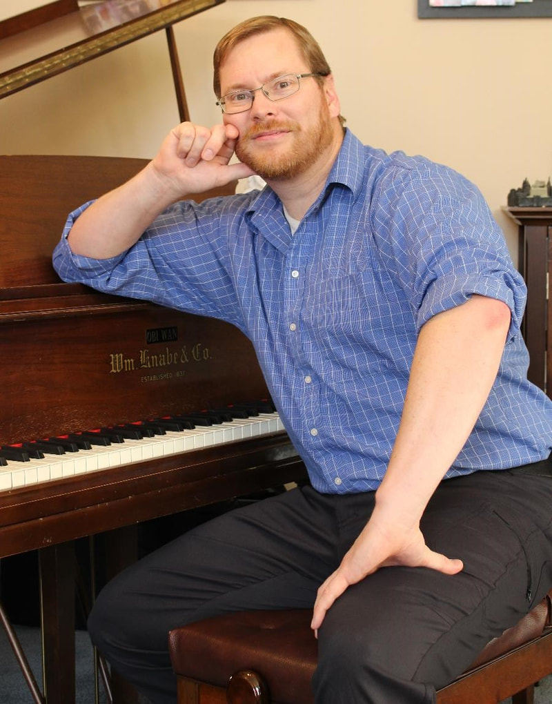 Doctor Octave's Piano Services - Mark Tolley posing at piano